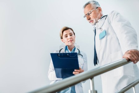 Photo for Attractive female doctor showing clipboard to serious male colleague on staircase in hospital - Royalty Free Image