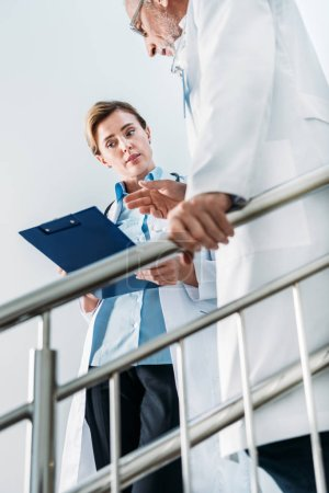 low angle view of female doctor talking and showing clipboard to male colleague on staircase in hospital