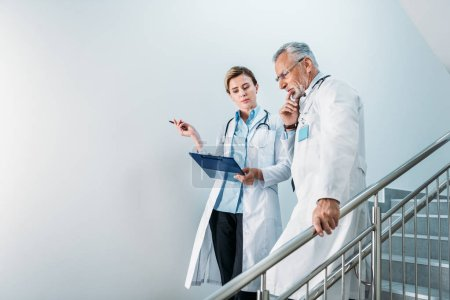 adult female doctor showing clipboard to thoughtful male colleague on staircase in hospital