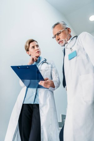 Photo for Low angle view of female doctor showing clipboard to male colleague on staircase in hospital - Royalty Free Image