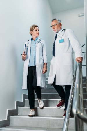 Photo for Male and female doctors with clipboard walking on staircase in hospital - Royalty Free Image
