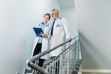 Photo pour Femme médecin montrant presse-papiers à collègue masculin sur escalier à l'hôpital - image libre de droit