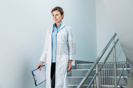 Photo for Smiling female doctor with clipboard walking on staircase in hospital - Royalty Free Image