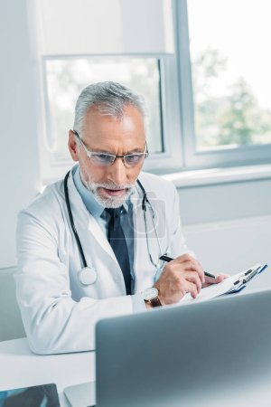 middle aged male doctor writing in clipboard and looking at laptop in office