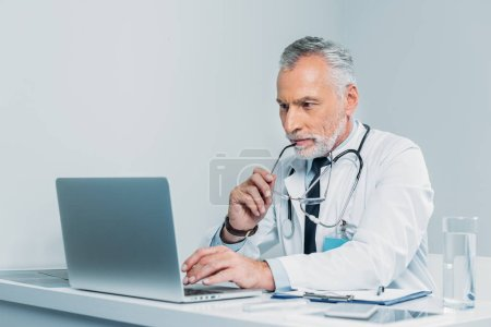middle aged male doctor holding eyeglasses and using laptop at table in office