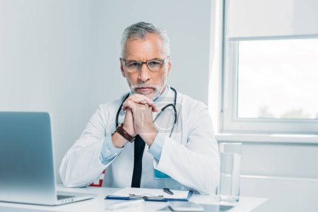 serious middle aged male doctor looking at camera at table with laptop in office
