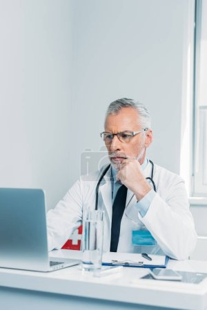 serious middle aged male doctor using laptop at table in office