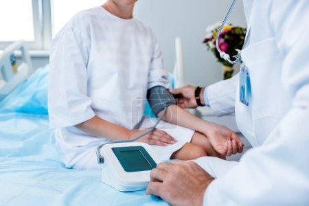 Photo pour Cropped image du médecin de sexe masculin mesure de la pression de la patiente par tonomètre dans chambre d'hôpital - image libre de droit