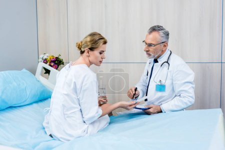 serious middle aged male doctor with stethoscope over neck pointing at pills to female patient in hospital room