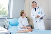 male doctor with stethoscope over neck pointing at clipboard to female patient in hospital room