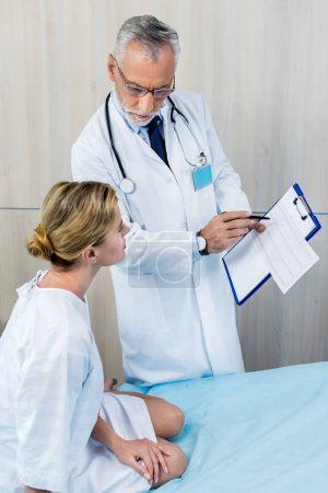 serious male doctor with stethoscope over neck pointing at clipboard to female patient in hospital room