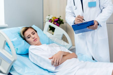 cropped image of male doctor with stethoscope over neck writing in clipboard near adult female patient in hospital room