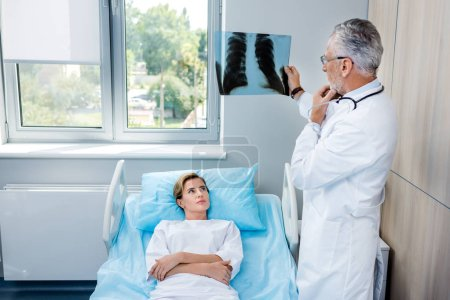 pensive male doctor analyzing x-ray picture near female patient in hospital room