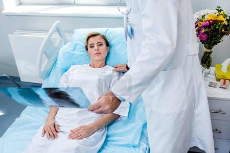 cropped image of male doctor holding x-ray picture and cheering up female patient in hospital room