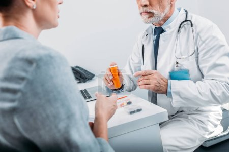 partial view of mature male doctor pointing at pills to female patient at table in office