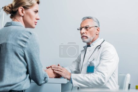 serious mature male doctor holding hands of female patient at table in office