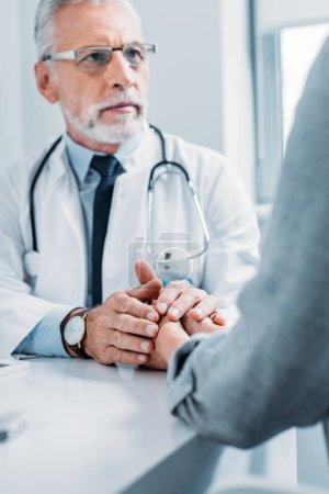 partial view of middle aged male doctor cheering up and holding hands of female patient at table in office
