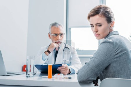 sad female patient looking away while mature male doctor sitting near at table in office