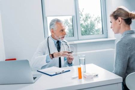 mature male doctor talking to female patient at table with laptop in office