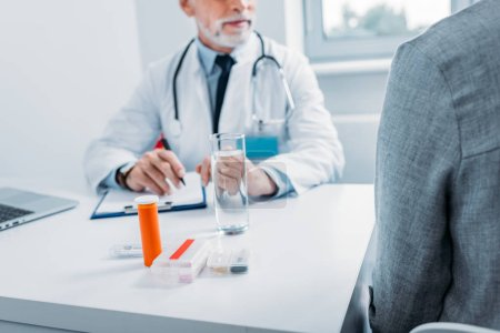 partial view of male doctor talking to female patient at table with pills and clipboard in office