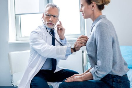 concentrated mature male doctor examining female patient by stethoscope in hospital room
