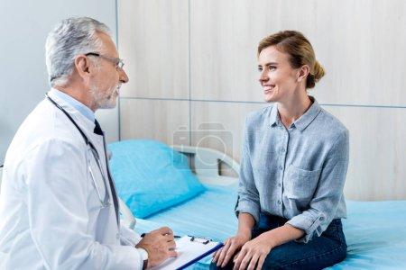 Photo pour Heureux mature médecin masculin écriture dans le presse-papiers près de patiente dans la chambre d'hôpital - image libre de droit
