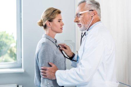 Photo pour Vue latérale du médecin masculin mature examinant le patient féminin par stéthoscope dans la chambre d'hôpital - image libre de droit