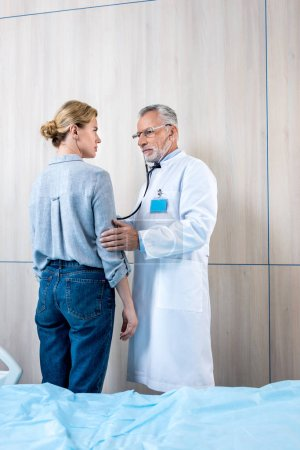 confident mature male doctor examining female patient by stethoscope in hospital room