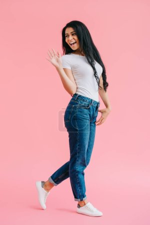 cheerful african american woman in casual clothing greeting someone on pink background