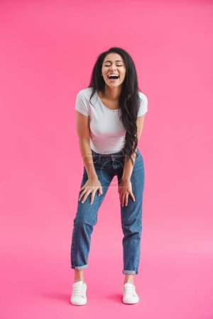 young african american woman laughing on pink background