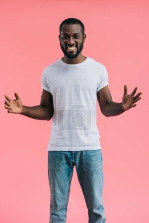 happy african american man with outstretched arms isolated on pink