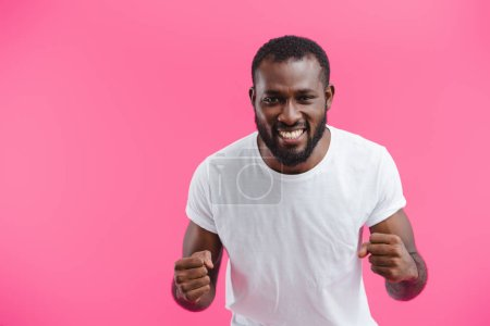 Photo for Portrait of smiling african american man showing fists isolated on pink - Royalty Free Image