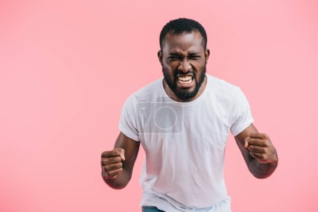 portrait of angry african american man in white shirt isolated on pink
