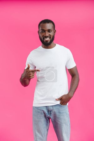 portrait of young smiling african american man pointing away isolated on pink