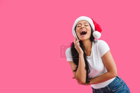 portrait of happy african american woman in santa claus hat talking on smartphone isolated on pink