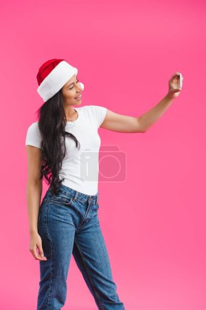 side view of smiling african american woman in santa claus hat taking selfie on smartphone isolated on pink