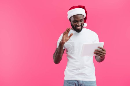portrait of smiling african american man in santa claus hat with tablet gesturing isolated on pink