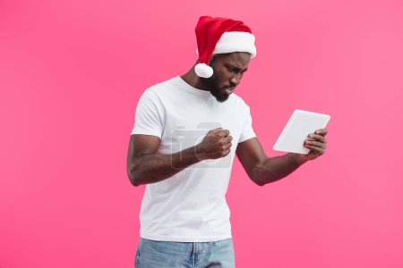 side view of angry young african american man in santa claus hat with tablet isolated on pink