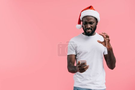 portrait of emotional african american man in santa claus hat using smartphone isolated on pink