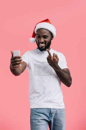 portrait of smiling african american man in santa claus hat with smartphone showing middle finger isolated on pink