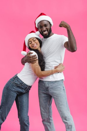 attractive african american woman in christmas hat embracing boyfriend while he showing muscles on hand isolated on pink background