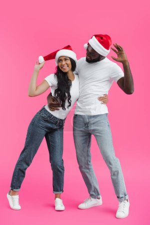 young african american couple in christmas hats embracing each other on pink background