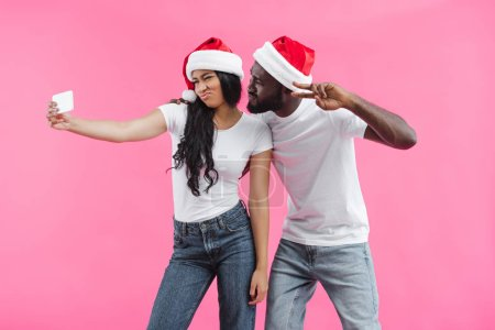 african american woman in christmas hat doing duck face and taking selfie on smartphone with boyfriend doing peace sign isolated on pink background