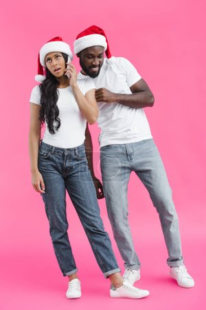 smiling african american man in chrismas hat eavesdropping girlfriend talking on smartphone on pink background