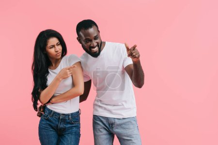 emotional african american couple pointing by fingers aside isolated on pink background