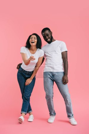 Photo for Laughing african american woman pointing at camera with boyfriend standing near on pink background - Royalty Free Image