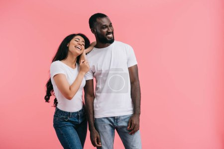 smiling young african american couple looking away isolated on pink background
