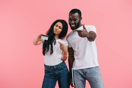 Photo for Emotional african american couple pointing at credit card isolated on pink background - Royalty Free Image