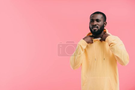 stylish young african american man taking off yellow hoodie isolated on pink background