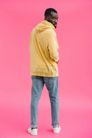 stylish african american man looking at camera on pink background